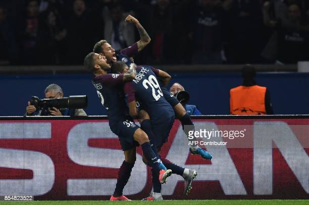TOPSHOT Paris SaintGermain's Brazilian forward Neymar is congratulated by Paris SaintGermain's Brazilian defender Dani Alves and Paris SaintGermain's...