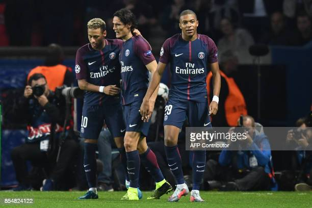 Paris SaintGermain's Brazilian forward Neymar is congratulated by Paris SaintGermain's Brazilian defender Dani Alves and Paris SaintGermain's French...