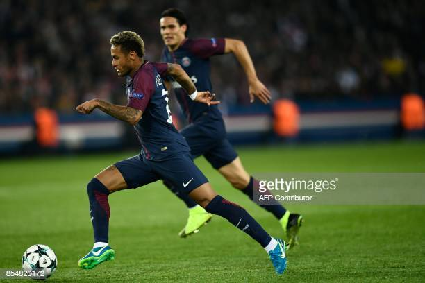 TOPSHOT Paris SaintGermain's Brazilian forward Neymar runs with the ball followed by Paris SaintGermain's Uruguayan forward Edinson Cavani during the...