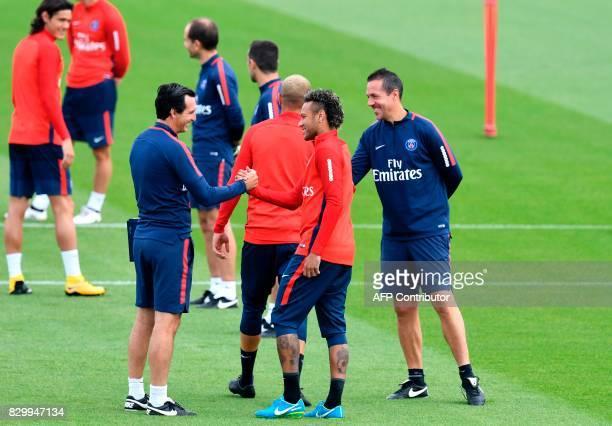 Paris SaintGermain's Brazilian forward Neymar shakes hands with Paris SaintGermain's Spanish head coach Unai Emery during a training session at the...