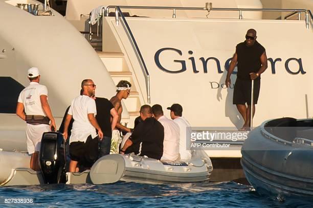 Paris SaintGermain's Brazilian forward Neymar stands before boarding a yacht as he leaves a beach in Ramatuelle southeastern France on August 7 2017...