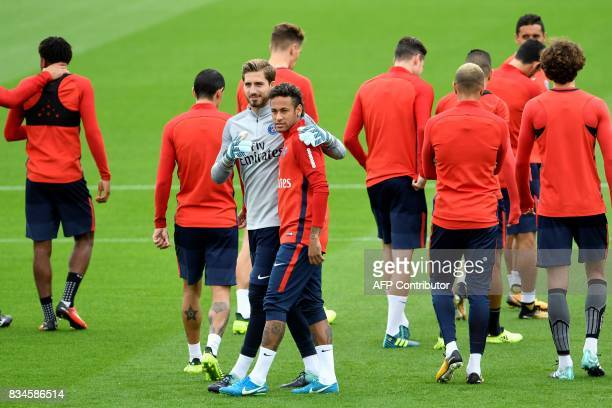 Paris SaintGermain's Brazilian forward Neymar talks with German goalkeeper Kevin Trapp during a training session at the Camp des Loges in...