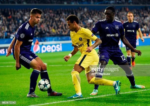 Paris SaintGermain's Brazilian forward Neymar vies with Anderlecht's Belgian midfielder Leander Dendoncker and Anderlecht's French defender Dennis...