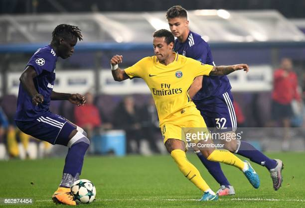 Paris SaintGermain's Brazilian forward Neymar vies with Anderlecht's Belgian midfielder Leander Dendoncker and Anderlecht's Nigerian forward Henry...