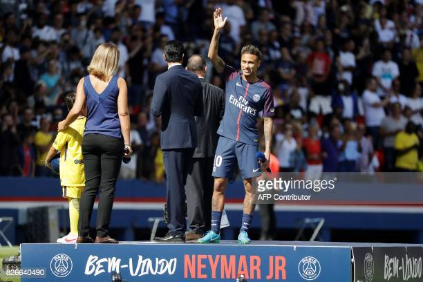 Paris SaintGermain's Brazilian forward Neymar waves to the crowd as he arrives on the football field during his presentation to the fans at the Parc...