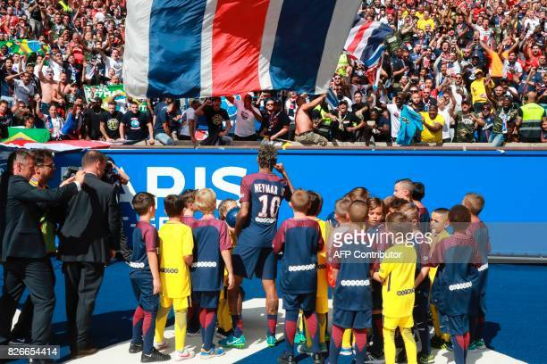 Paris SaintGermain's Brazilian forward Neymar waves to the crowd during his presentation to the fans at the Parc des Princes stadium in Paris on...
