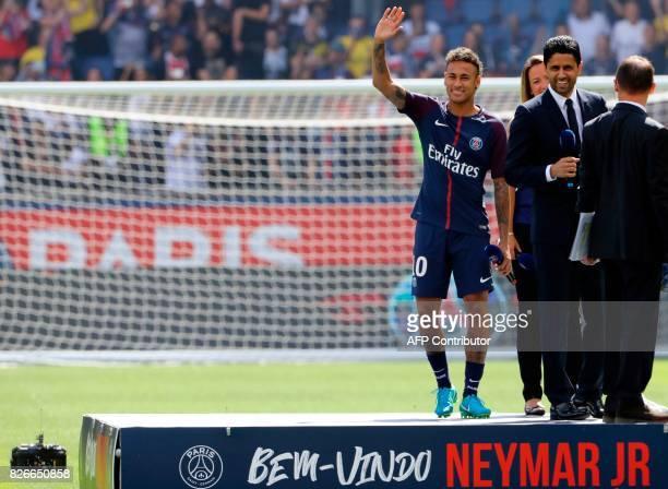 Paris SaintGermain's Brazilian forward Neymar waves to the crowd next to Paris Saint Germain's Qatari president Nasser AlKhelaifi during the player's...