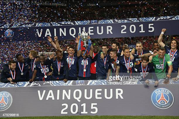 Paris SaintGermain's Brazilian midfielder Lucas Moura holds the French Cup trophy as Paris SaintGermain's players celebrate after winning the French...