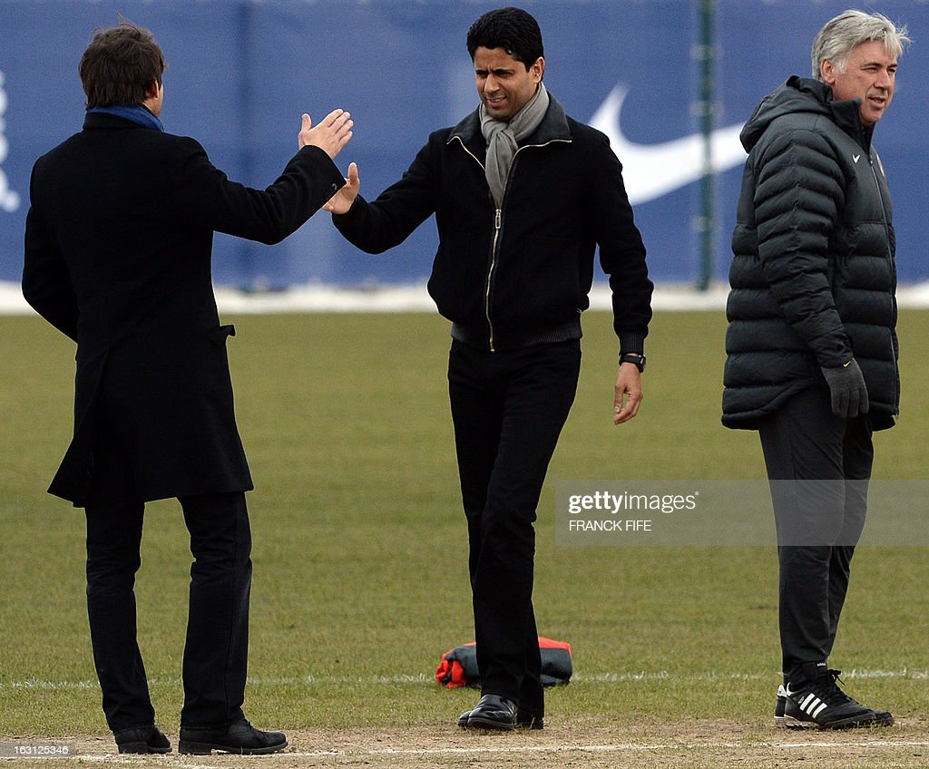Paris Saint-Germain's Brazilian sporting director Leonardo (L) shakes hands with Qatari Chairman Nasser Al-Khelaifi (C) as Italian coach Carlo Ancelotti looks on during a training session on March 5, 2013 at the Parc des Princes stadium in Paris, on the eve of an UEFA Champions League round of 16 second leg football match against Valencia.