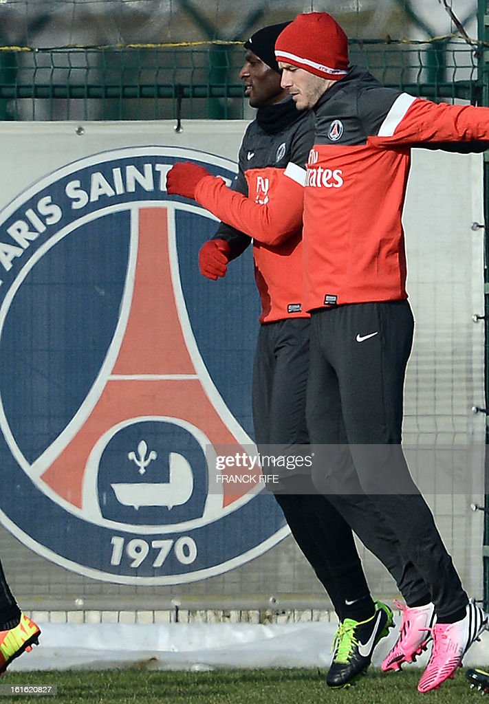Paris Saint-Germain's British midfielder David Beckham (R) and defender Zoumana Camara attend a training session on February 13, 2013 at the club's Camp des Loges training center in Saint-Germain-en-Laye, near Paris. Beckham, PSG's latest prized signing, is taking part in his first full training session today, with the view to possibly making his debut in February 17's L1 match at Sochaux. AFP PHOTO / FRANCK FIFE