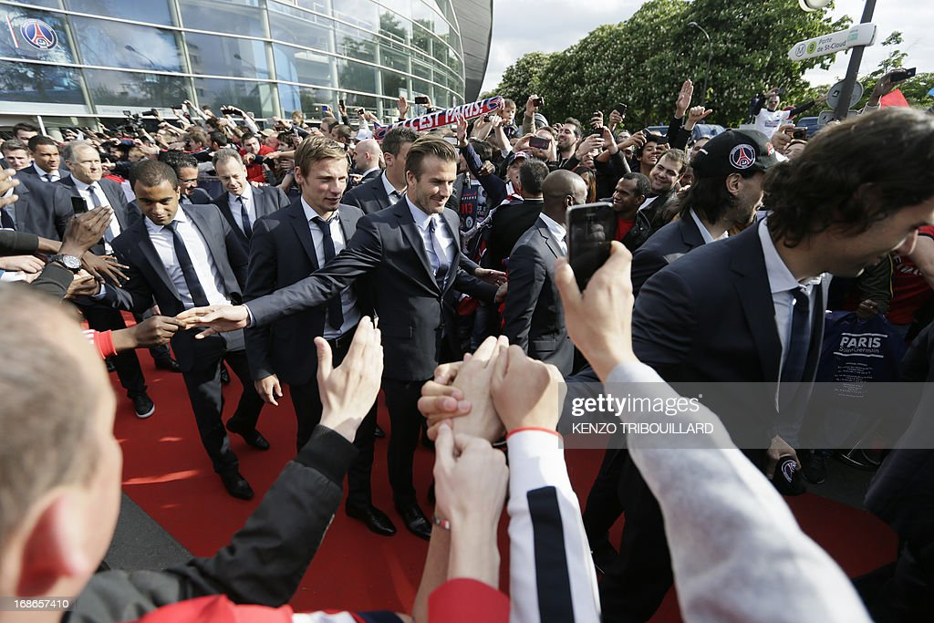 Paris Saint-Germain's British midfielder David Beckham (C) shakes hands with supporters as he arrives with the squad to parade in a double decker, on May 13, 2013 in Paris, one day after Paris secured French L1 football championship title.