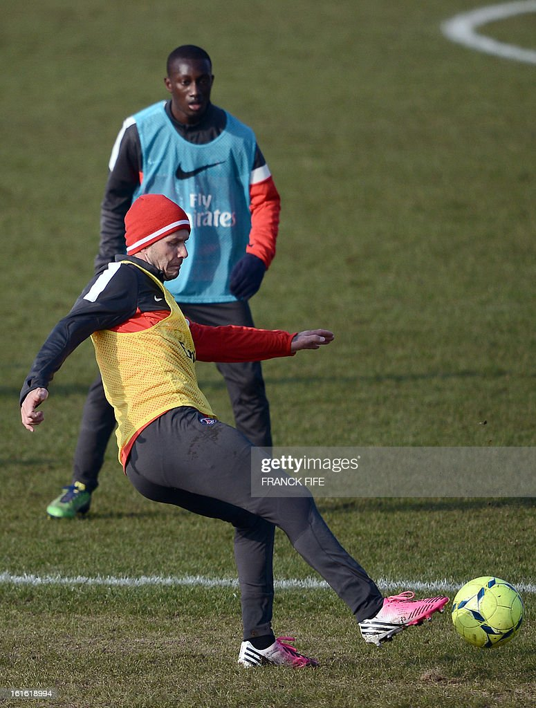 Paris Saint-Germain's British midfielder David Beckham (front) shots a ball in front of French defender Antoine Conte during a training session on February 13, 2013 at the club's Camp des Loges training center in Saint-Germain-en-Laye, near Paris. Beckham, PSG's latest prized signing, is taking part in his first full training session today, with the view to possibly making his debut in February 17's L1 match at Sochaux.