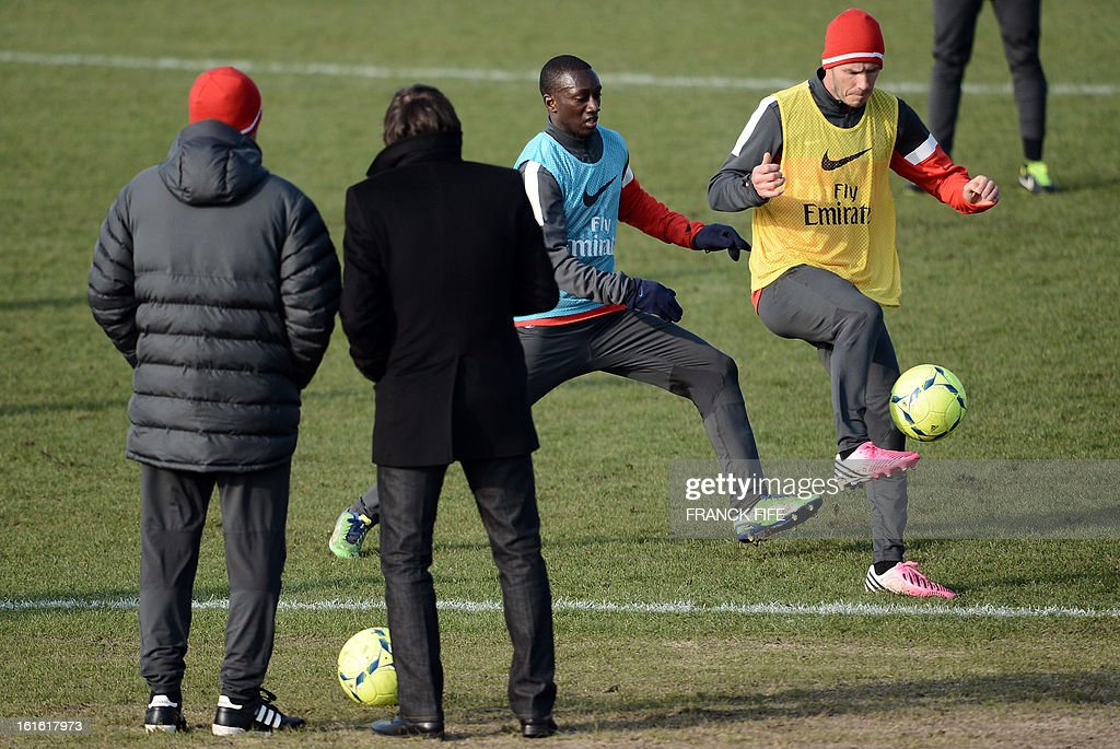 Paris Saint-Germain's British midfielder David Beckham (R) vies with defender Antoine Conte as Italian coach Carlo Ancelotti (L) and Brazilian sport director Leonardo watch during a training session on February 13, 2013 at the club's Camp des Loges training center in Saint-Germain-en-Laye, near Paris. Beckham, PSG's latest prized signing, is taking part in his first full training session today, with the view to possibly making his debut in February 17's L1 match at Sochaux.