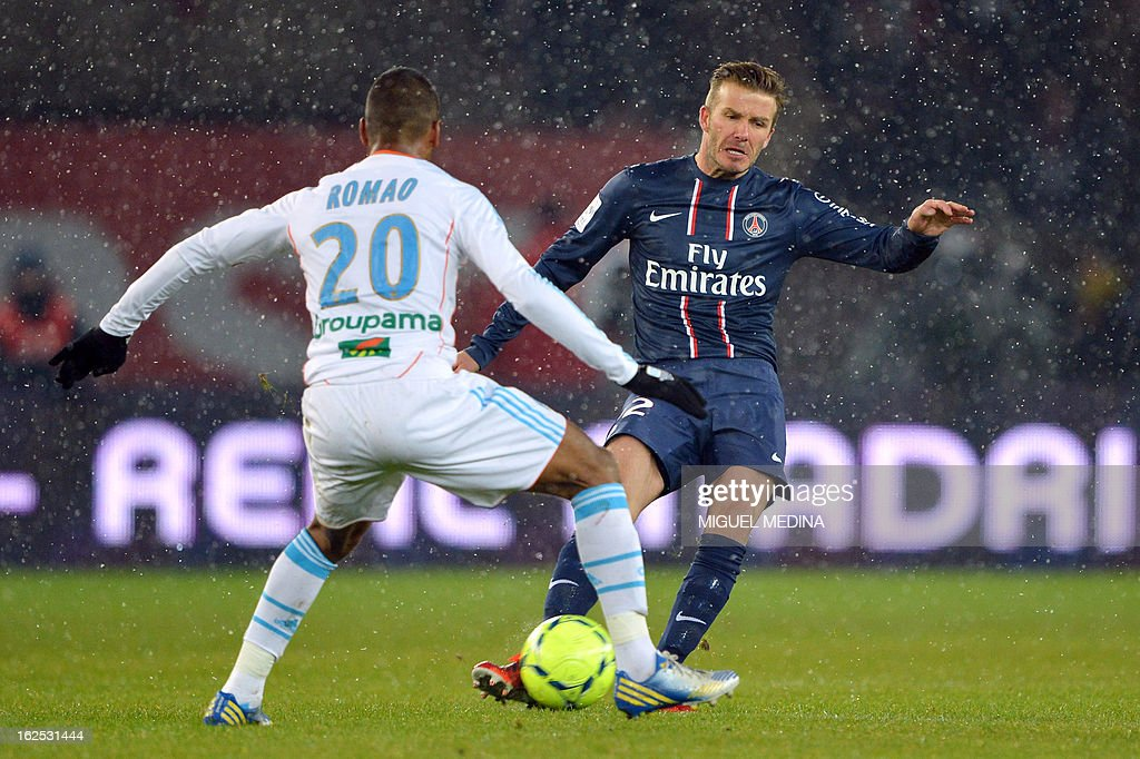 Paris Saint-Germain's British midfielder David Beckham (R) vies with Marseille's French forward Alaixys Romao during the French L1 football match Paris Saint-Germain (PSG) vs Olympique de Marseille (OM) on February 24, 2013 at the Parc des Princes stadium in Paris. AFP PHOTO MIGUEL MEDINA