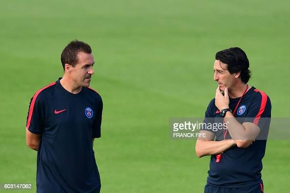 Paris SaintGermain's coach Unai Emery speaks with his assistant Juan Carlos during his team training session on the eve of the UEFA Champions League...