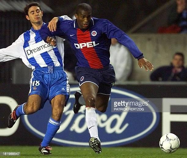 Paris SaintGermain's defender Sylvain Distin beats Deportivo La Coruna's midfielder Victor to the ball during their 2nd round Champions League match...