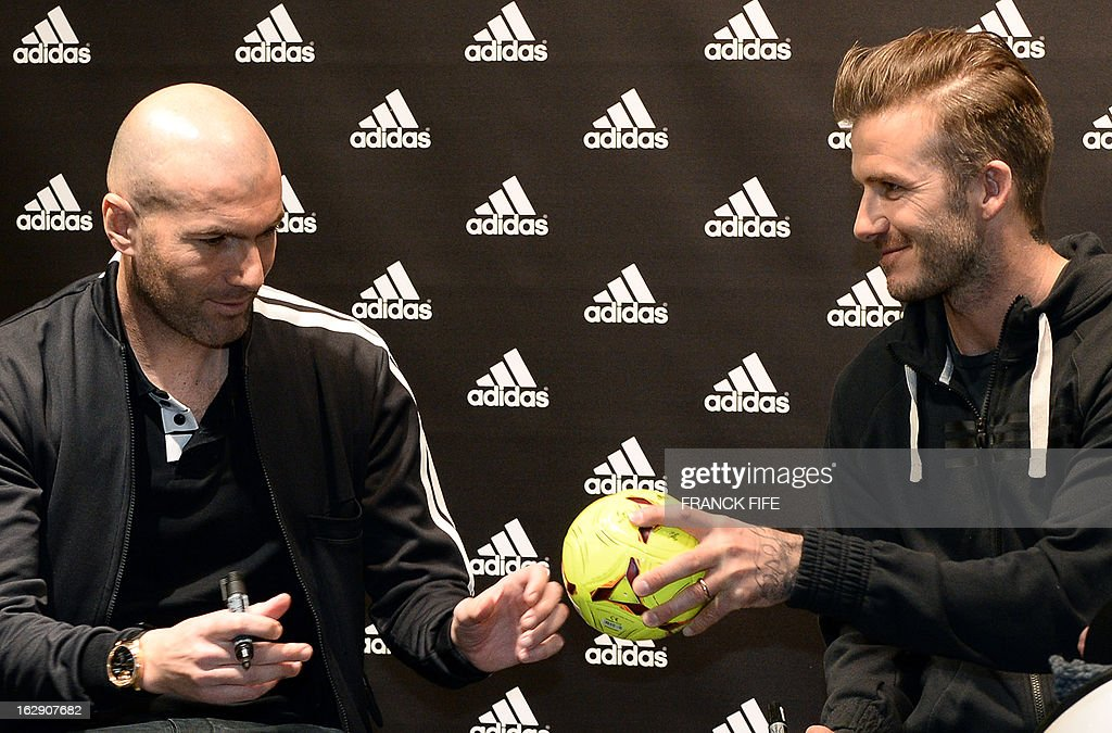 Paris Saint-Germain's (PSG) English midfielder David Beckham (R) and French former international player Zinedine Zidane signs autographs in a store of their sponsor on the Champs-Elysees avenue in Paris, on February 28, 2013. Beckham and Zidane have autographed balls and jerseys for thirty fans selected via Twitter. AFP PHOTO/ FRANCK FIFE