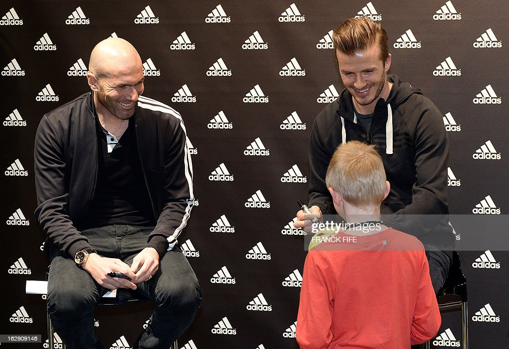 Paris Saint-Germain's (PSG) English midfielder David Beckham (R) and French former international player, Zinedine Zidane prepare for a photocall in a store of their sponsor on the Champs-Elysees in Paris, on February 28, 2013. Beckham and Zidane have autographed balls and jerseys for thirty fans selected via Twitter.