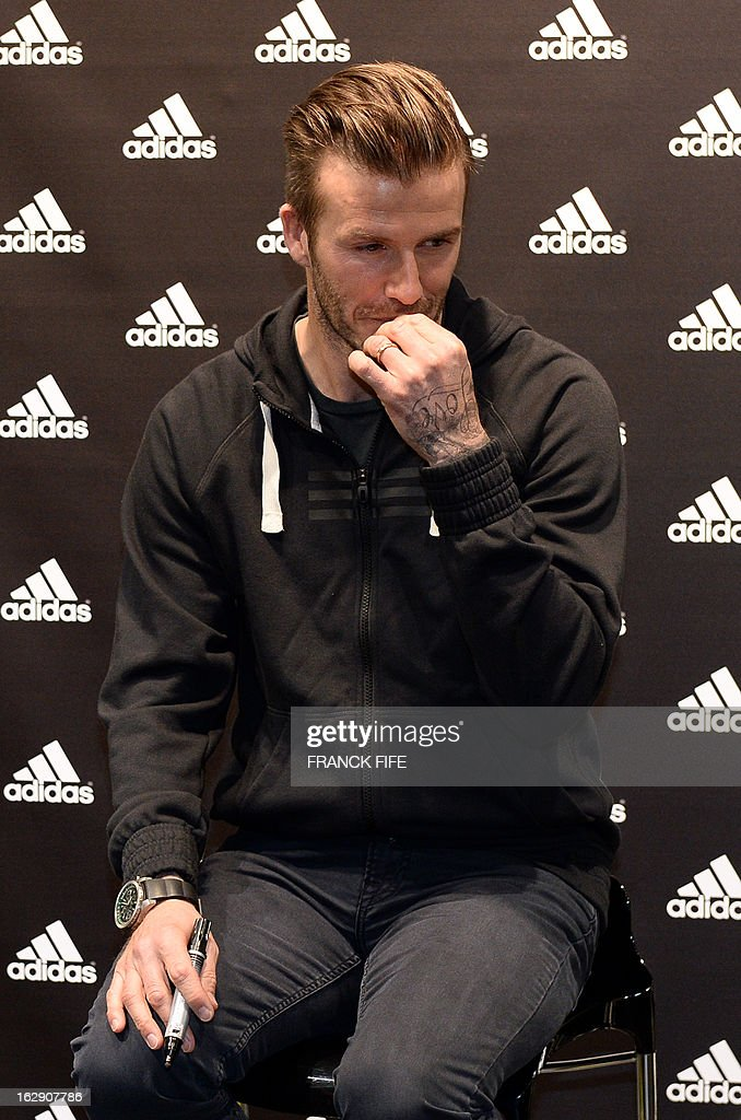 Paris Saint-Germain's (PSG) English midfielder David Beckham is pictured in a store of his sponsor on the Champs-Elysees avenue in Paris, on February 28, 2013. Beckham and French former international player Zinedine Zidane have autographed balls and jerseys for thirty fans selected via Twitter.