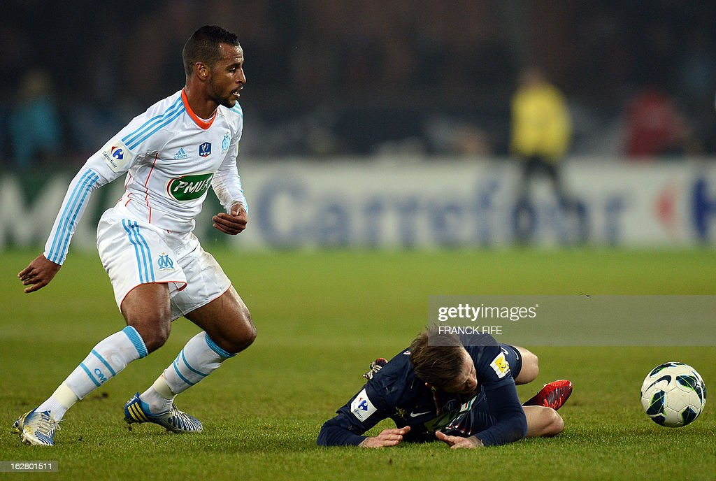 Paris Saint-Germain's English midfielder David Beckham is tackled by Marseille's midfielder Jacques Romao during the French Cup football match Paris Saint-Germain (PSG) vs Olympique de Marseille (OM) on February 27, 2013 at the Parc-des-Princes stadium in Paris.
