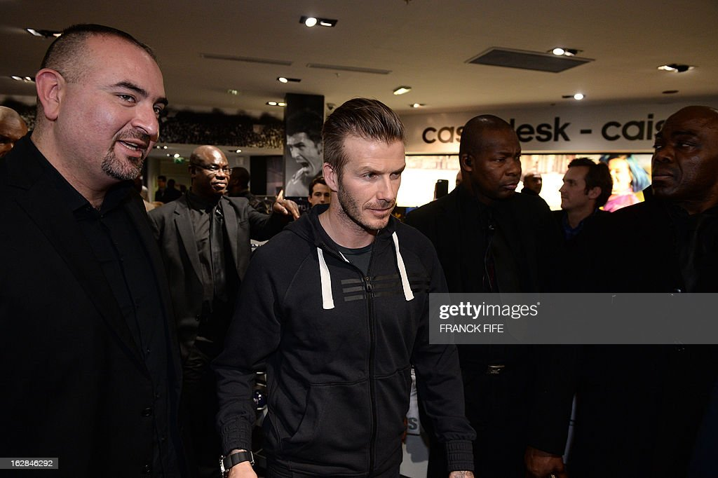 Paris Saint-Germain's (PSG) English midfielder David Beckham (C) leaves a store of his sponsor on the Champs-Elysees avenue after taking part in an event for fans, on February 28, 2013 in Paris. Beckham and French former international player Zinedine Zidane have autographed balls and jerseys for thirty fans selected via Twitter.