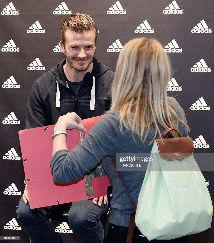 Paris Saint-Germain's (PSG) English midfielder David Beckham meets fans in front of a store of his sponsor on the Champs-Elysees avenue in Paris, on February 28, 2013. Beckham and French former international player Zinedine Zidane have autographed balls and jerseys for thirty fans selected via Twitter.