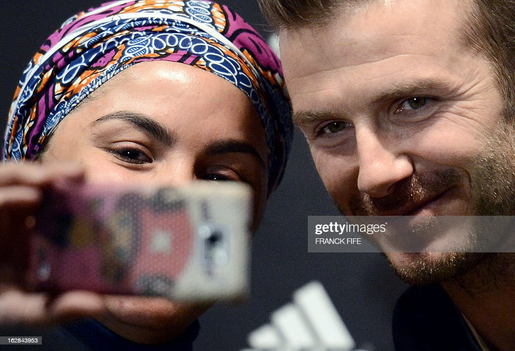 Paris Saint-Germain's (PSG) English midfielder David Beckham (R) poses with a fan in front of a store of his sponsor on the Champs-Elysees avenue in Paris, on February 28, 2013. Beckham and French former international player Zinedine Zidane have autographed balls and jerseys for thirty fans selected via Twitter.