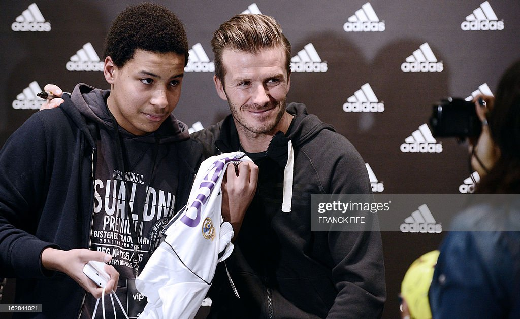 Paris Saint-Germain's (PSG) English midfielder David Beckham (C) poses with a fan in front of a store of his sponsor on the Champs-Elysees avenue in Paris, on February 28, 2013. Beckham and French former international player Zinedine Zidane have autographed balls and jerseys for thirty fans selected via Twitter.