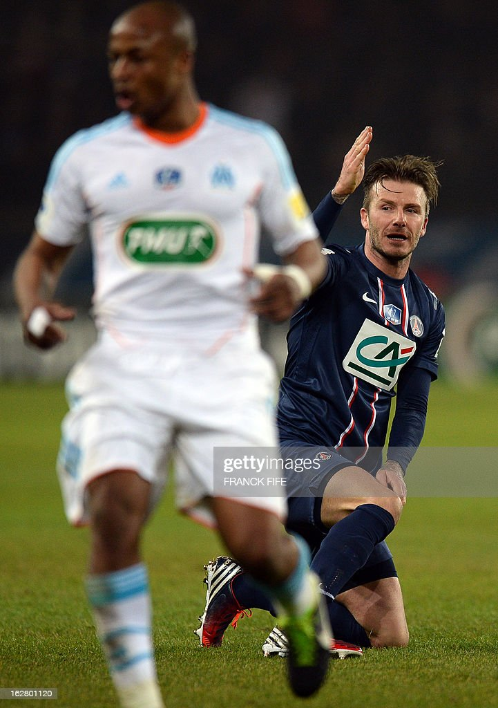 Paris Saint-Germain's English midfielder David Beckham (R) reacts behind Marseille's Ghanaian forward Andre Ayew during the French Cup football match Paris Saint-Germain vs Marseille, on February 27, 2013 at the Parc des Princes stadium in Paris. AFP PHOTO/ FRANCK FIFE