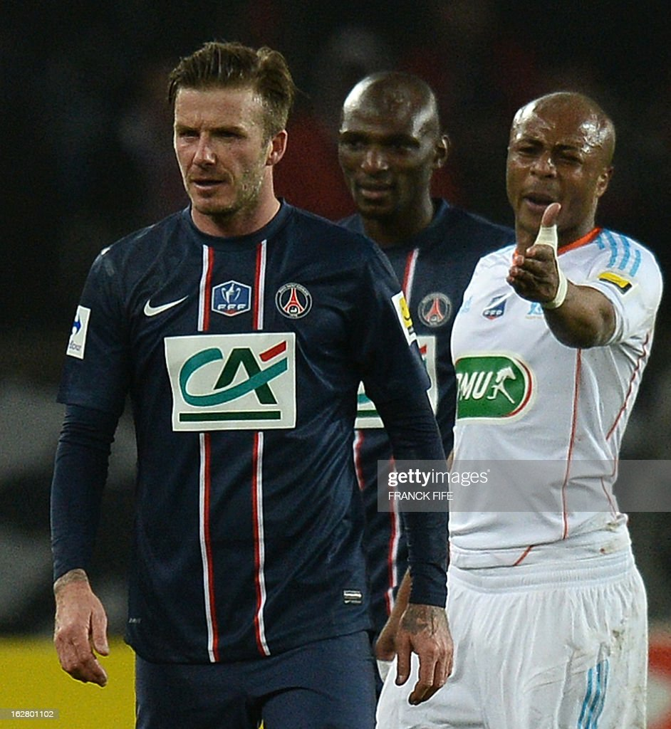 Paris Saint-Germain's English midfielder David Beckham (L) reacts in front Marseille's Ghanaian forward Andre Ayew during the French Cup football match Paris Saint-Germain vs Marseille February 27, 2013 at the Parc des Princes stadium in Paris.