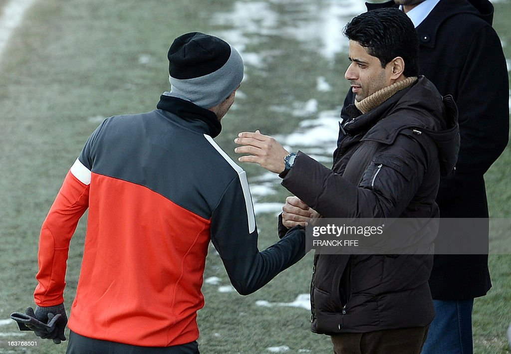 Paris Saint-Germain's English midfielder David Beckham (L) shakes hands with Chairman of the Paris Saint-Germain L1 football club, Nasser Al-Khelaifi after a training session, on March 15, 2013 at the Camp des Loges, the PSG football club training center in Saint-Germain-en-Laye, west of Paris.