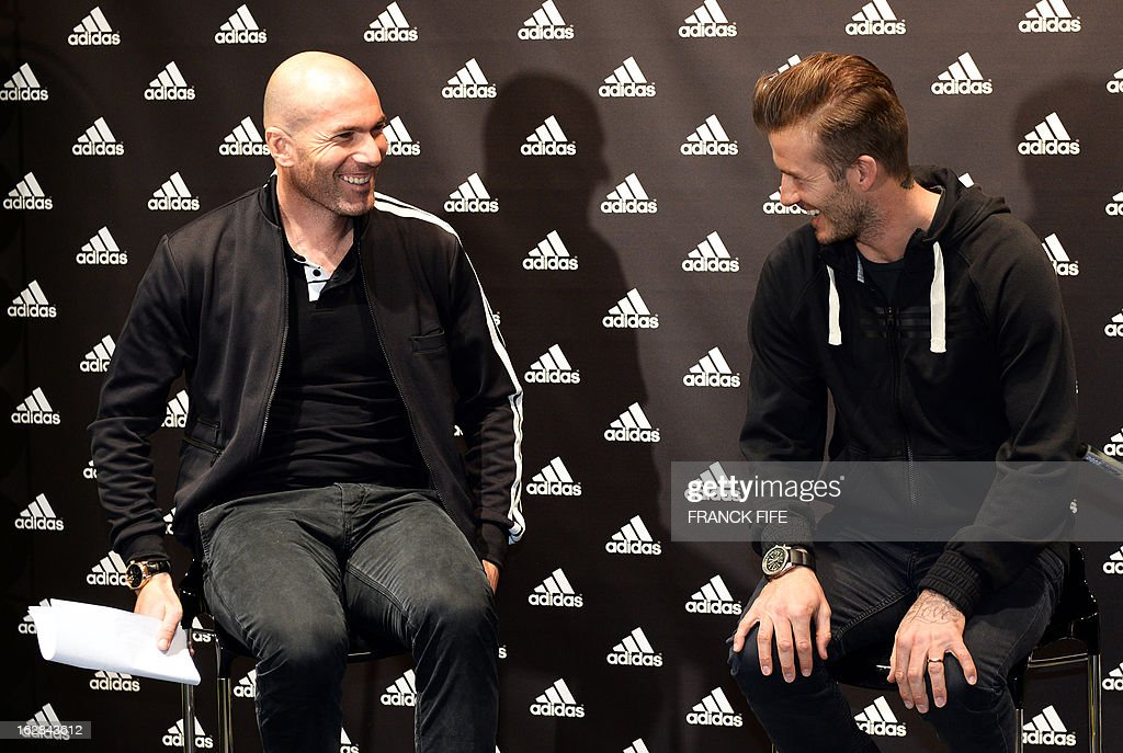Paris Saint-Germain's (PSG) English midfielder David Beckham (R) shares a laugh with French former international player, Zinedine Zidane in a store of their sponsor on the Champs-Elysees avenue in Paris, on February 28, 2013. Beckham and Zidane have autographed balls and jerseys for thirty fans selected via Twitter.