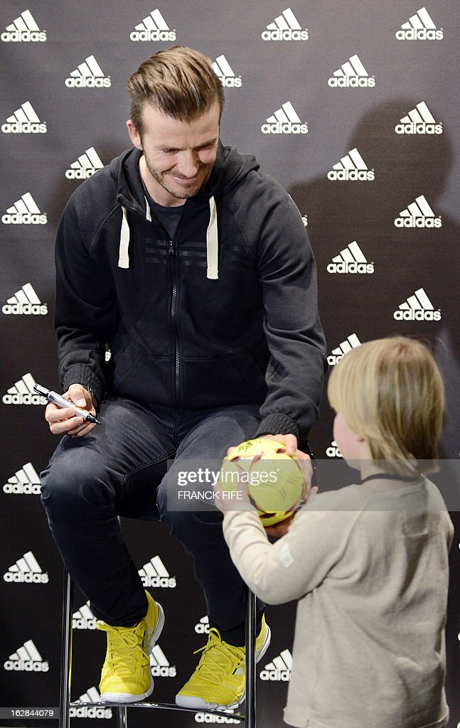 Paris Saint-Germain's (PSG) English midfielder David Beckham signs an autograph in front of a store of his sponsor on the Champs-Elysees avenue in Paris, on February 28, 2013. Beckham and French former international player Zinedine Zidane have autographed balls and jerseys for thirty fans selected via Twitter.