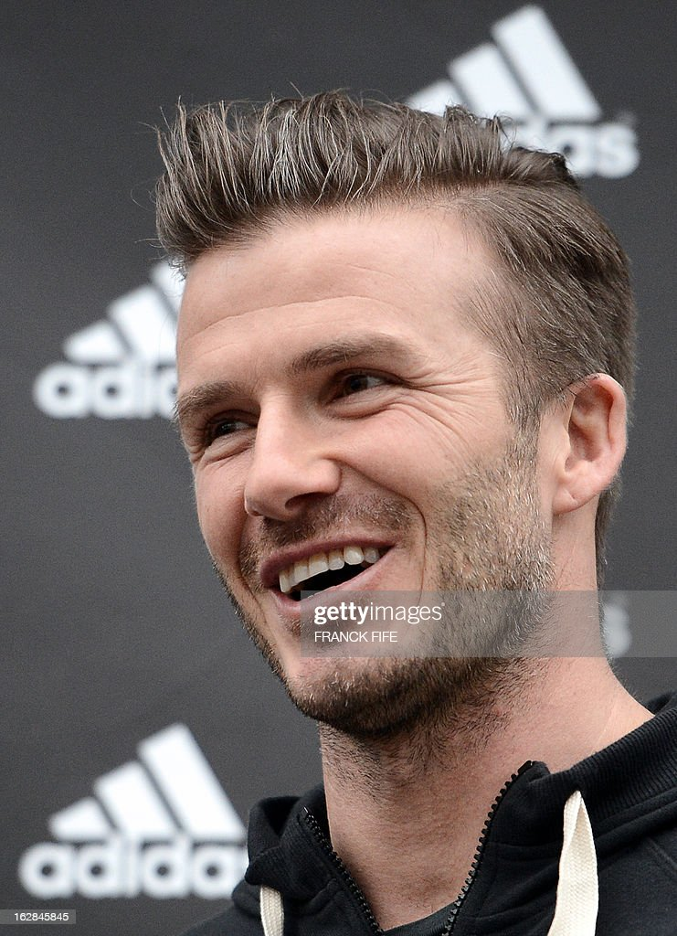 Paris Saint-Germain's (PSG) English midfielder David Beckham smiles as he takes part in an event for fans in front of a store of his sponsor on the Champs-Elysees avenue in Paris, on February 28, 2013. Beckham and French former international player Zinedine Zidane have autographed balls and jerseys for thirty fans selected via Twitter.