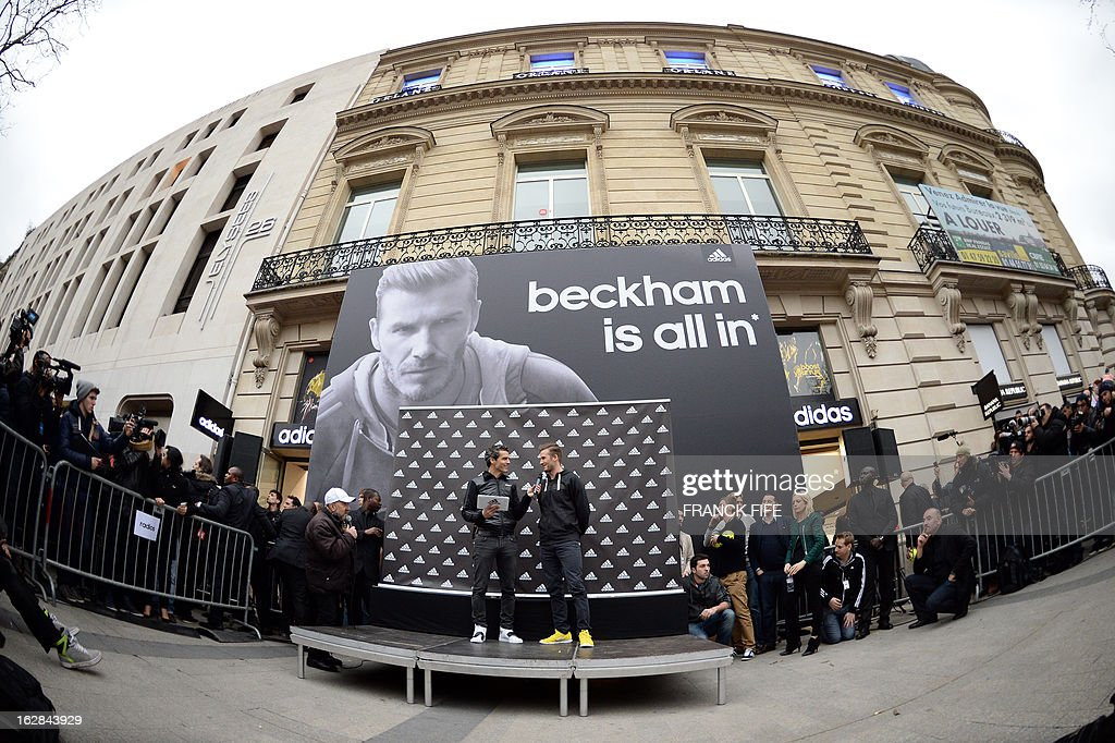 Paris Saint-Germain's (PSG) English midfielder David Beckham (C-R) takes part in an event for fans in front of a store of his sponsor on the Champs-Elysees avenue in Paris, on February 28, 2013. Beckham and French former international player Zinedine Zidane have autographed balls and jerseys for thirty fans selected via Twitter.