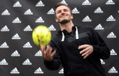 Paris SaintGermain's English midfielder David Beckham throws a ball to fans in a store of his sponsor on the ChampsElysees avenue in Paris on...