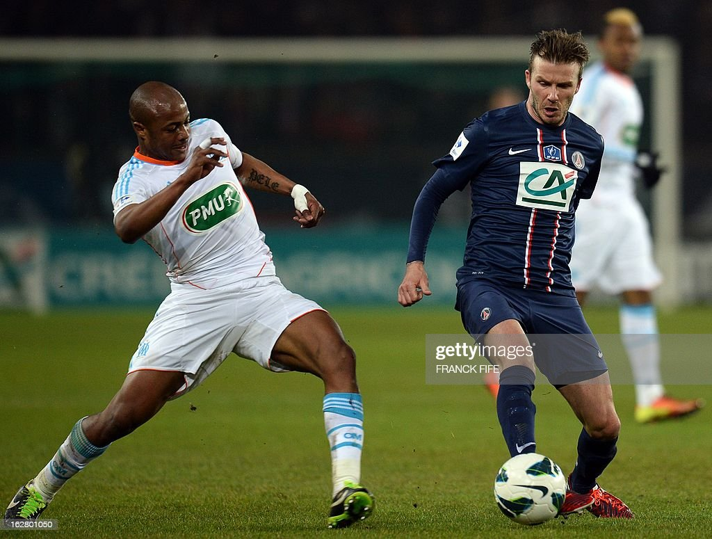 Paris Saint-Germain's English midfielder David Beckham (R) vies with Marseille's Ghanaian forward Andre Ayew during the French Cup football match Paris Saint-Germain (PSG) vs Olympique de Marseille (OM) on February 27, 2013 at the Parc-des-Princes stadium in Paris.