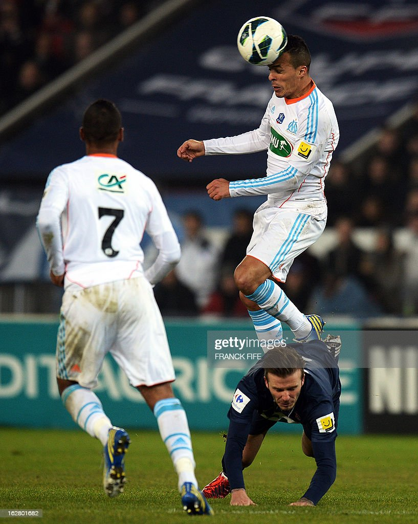 Paris Saint-Germain's English midfielder David Beckham (down) vies with Marseille's midfielder Foued Kadir (up) during the French Cup football match Paris Saint-Germain (PSG) vs Olympique de Marseille (OM) on February 27, 2013 at the Parc-des-Princes stadium in Paris.