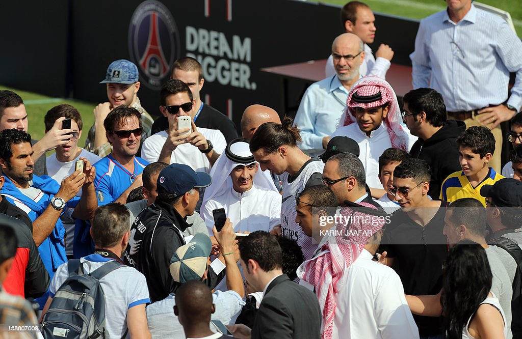 Paris Saint-Germain's forward Zlatan Ibrahimovic (C) signs autographs for fans following a training session at the Aspire Academy of Sports Excellence in the Qatari capital Doha on December 30, 2012. PSG is in Qatar for a week-long training camp before the resumption of the French Ligue 1 after the winter break.