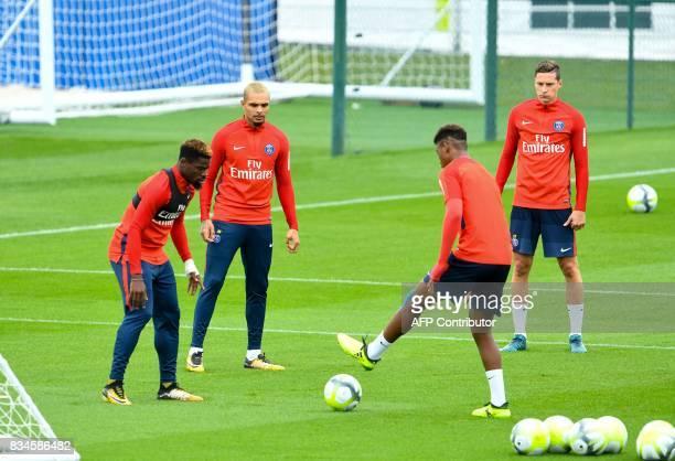 Paris SaintGermain's French defender Layvin Kurzawa and midfielder Julian Draxler watch as Ivorian defender Serge Aurier eyes the ball during a...