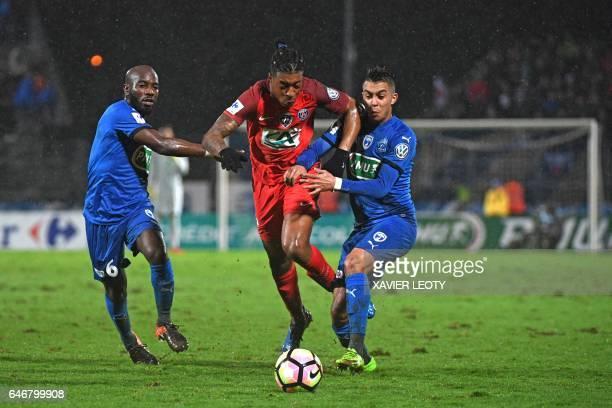 Paris SaintGermain's French defender Presnel Kimpembe outruns Niort's French forward Zakaria Grich and Niort's French midfielder Alliou Dembele...