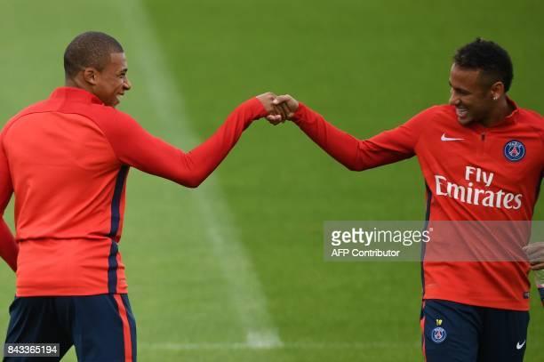 TOPSHOT Paris SaintGermain's French forward Kylian Mbappe and Paris SaintGermain's Brazilian forward Neymar shake hands as they take part in a...