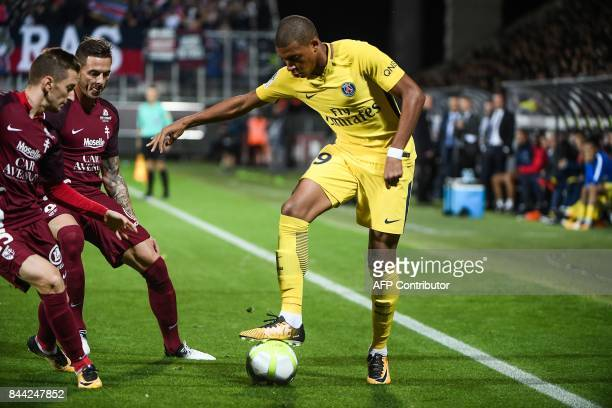 Paris SaintGermain's French forward Kylian Mbappe controls the ball next to Metz's French forward Nolan Roux during the French L1 football match...