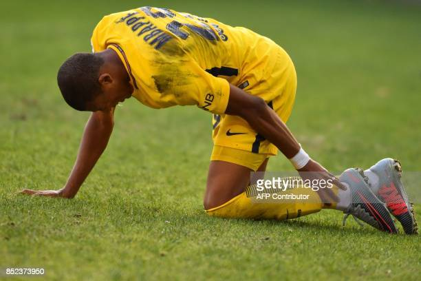 Paris SaintGermain's French forward Kylian Mbappe holds his ankle in pain during the French Ligue 1 football match between Paris SaintGermain and...