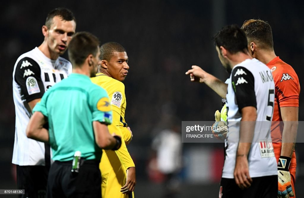 Paris Saint-Germain's French forward Kylian MBappe (C) reacts next to Angers' French midfielder Thomas Mangani (R) during the French L1 Football match between Angers (SCO) and Paris Saint-Germain (PSG), on November 4, 2017, in Raymond Kopa Stadium, in Angers, northwestern France. /