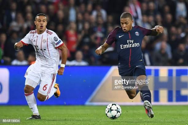Paris SaintGermain's French forward Kylian Mbappe runs ahead of Bayern Munich's Spanish midfielder Thiago Alcantara during the UEFA Champions League...