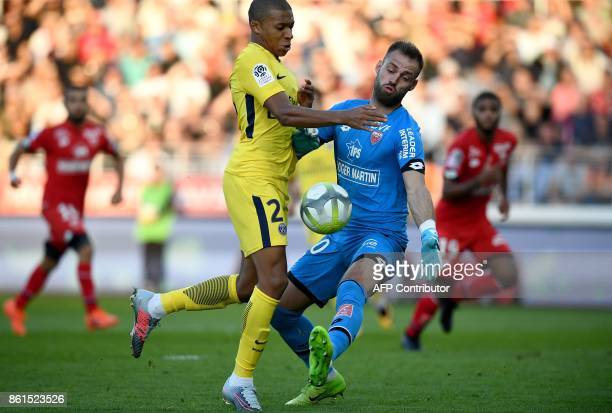 Paris SaintGermain's French forward Kylian Mbappe vies with Dijon's French goalkeeper Baptiste Reynet during the French L1 football match between...