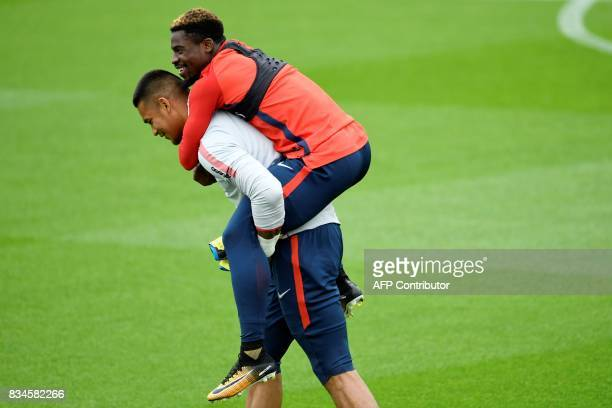 Paris SaintGermain's French goalkeeper Alphonse Areola carries Ivorian defender Serge Aurier on his back during a training session at the Camp des...