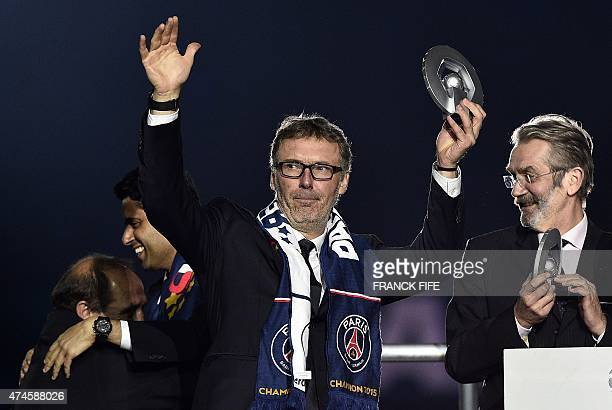 Paris SaintGermain's French head coach Laurent Blanc holds the trophy on the podium after winning the French L1 title at the end of the French L1...