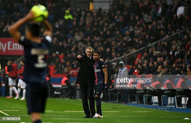 Paris SaintGermain's French head coach Laurent Blanc speaks with midfielder Christopher Nkunku during the French L1 football match between Paris...
